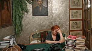 Interior of a room with Stalin memorabilia including paintings and books.