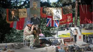 A man sells flags and posters of Soviet leaders at Tbilisi's flea market.