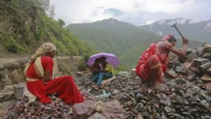 Workers repair a road damaged by a landslide in Uttarakhand