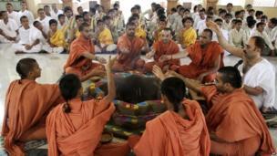"Students of Swaminarayan Gurukul Vishwavidhya Pratishthanam (SGVP) perform rituals during a ""yagya,"" or a fire ritual, to pray for the Uttarakhand flood victims in"