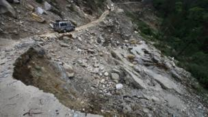 Vehicle moves along a damaged road caused by landslides, in Gaucha, Uttarakhand