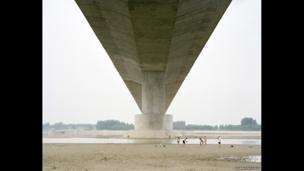 People play by the river under a bridge in Shandong
