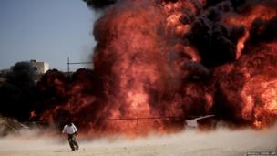 An Iranian man runs away after setting ablaze 50 tonnes of drugs seized in recent months in eastern Tehran