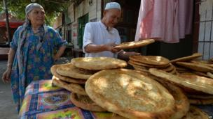 Ethnic Uighurs display bread at their stall beside the road leading into the riot affected town of Lukqun, Xinjiang Province on 27 June 2013
