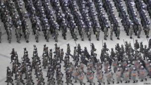 Armed paramilitary policemen run in formation during a gathering to mobilize security operations in Urumqi, Xinjiang Uighur Autonomous Region, on 29 June 2013