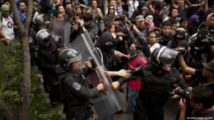 Mexican police try to control a crowd during a march to protest against reform of Pemex, Monday, 1 July