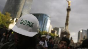 """A demonstrator wears a helmet with a sticker that reads """"Pemex is not for sale"""" during a protest against the privatisation of the state oil monopoly Pemex in Mexico City, 1 July"""