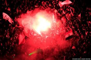Protesters opposing President Mohamed Morsi gather around a lit flare