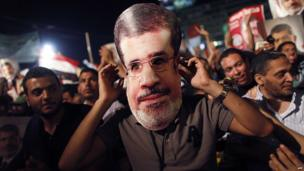 A supporter of ousted Egyptian President Mohammed Morsi wears a cut-out of his face as a mask