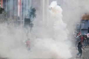 A protester throws a tear gas canister thrown by a police officer, during a demonstration against the government in Lim
