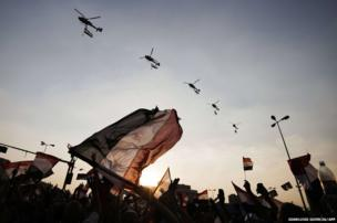 "Egyptian people wave the national flag as army helicopters fly above Egypt""s landmark Tahrir square"