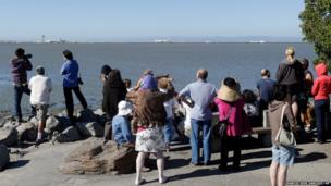 People gather at a lookout point to get a view of the wreckage of Asiana Flight 214 at the San Francisco International Airport