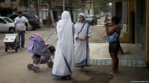 Two nuns talk to a woman on the streets of Varginha
