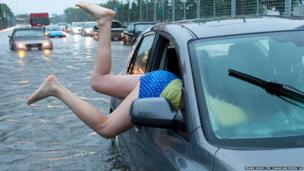 A woman gets back into her flooded car on the Toronto Indy course on Lakeshore Boulevard in Toronto