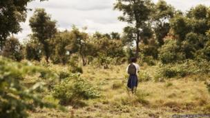 Tanzanian schoolgirl Sylvia walking through the bush
