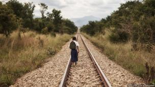 Tanzanian schoolgirl Sylvia walking along a railway