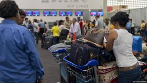 People queue waiting for their flights at Mexico City's Benito Juarez airport on 5 July