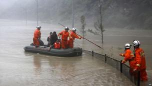 This picture taken on 9 July 2013 shows rescuers looking for victims as heavy flood waters sweep through Beichuan in south-west China's Sichuan province