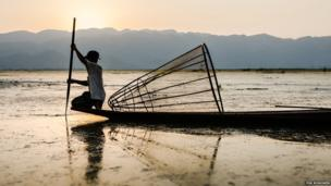 A fisherman on Inle Lake at sunset in Burma