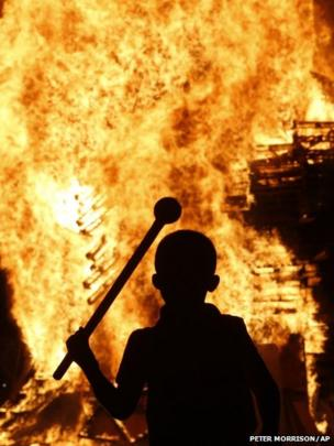 A boy watches a bonfire in the Protestant Sandy Row area of Belfast, Northern Ireland