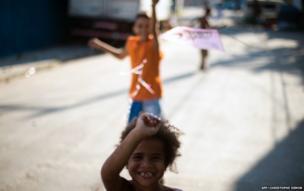 Children play with a kite in Varginha, part of the Manguinhos shantytown complex, in Rio de Janeiro, 8 July
