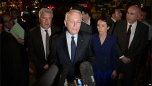 French Prime Minister Jean-Marc Ayrault (C) speaks to the press during a visit to the site of a train accident on 12 July 2013
