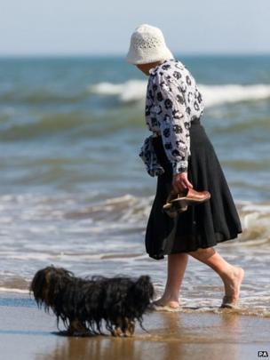 A woman walking her dog on a beach in Scarborough, North Yorkshire, as England and Wales are preparing to bask in scorching temperatures today as the hottest day of the year so far arrives.