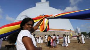 A Buddhist flag is held up high outside a temple in Anuradhapura, Sri Lanka.