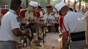 French Foreign Legion soldiers share champagne prior to the start of the traditional Bastille day military parade.