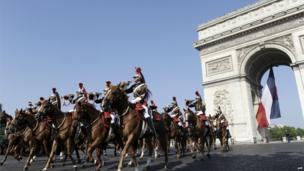 Republican Guard riders pass the Arch of Triumph on the Place de l'Etoile.