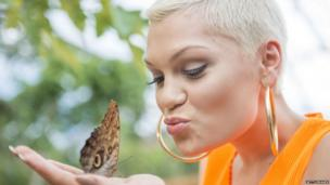 Jessie J with a butterfly in her hand