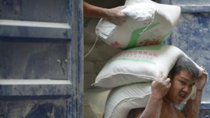 Workers unload flour on a street in Shanghai, China