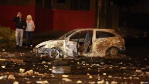 People walk past a burnt car in Belfast