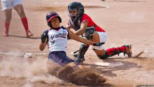 Misato Kawano of Japan is tagged out by Venezuela's catcher Miagros Lozada during the Canadian Open Fastpitch International baseball championship