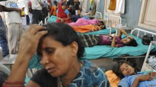 Mother Asha Devi sits with her hand on her head next to her sick daughter at a hospital in the eastern city of Patna on 17 July 2013