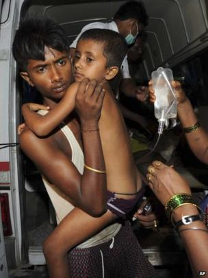 An Indian man carries a boy on a drip out of an ambulance in Patna on 17 July 2013.