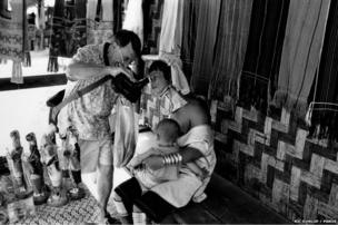 A tourist shows a video to a Padaung mother
