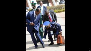 Ivorian President Alassane Ouattara (L) having his trouser leg adjusted, Abuja, Nigeria - Wednesday 17 July 2013