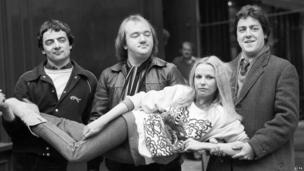 (l-r) Rowan Atkinson, Mel Smith, and Griff Rhys Jones carrying Pamela Stephenson.
