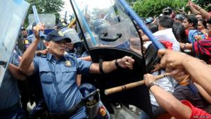 Policemen hit anti government protesters