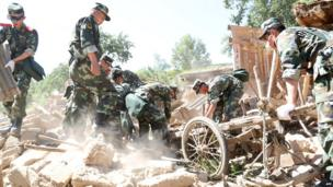 Rescuers use a wooden cart to search for survivors in the ruins of a damaged house in Hetuo township in China's north-west Gansu province following two earthquakes on 22 July, 2013.