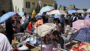 Residents holding umbrellas gather at a makeshift hospital after an earthquake hit Minxian county in north-west China's Gansu province on Monday 22 July 2013.