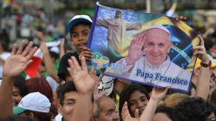 Pilgrims wait across the city for Pope Francis to pass in an open-top jeep after his arrival in Rio de Janeiro on July 22, 2013
