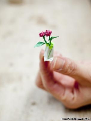 Origami artist Toma Takeda displays a tiny origami rose