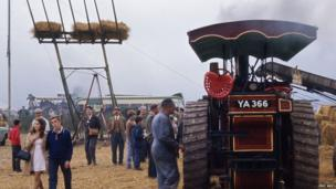 Crowds and vintage vehicles at 1968 fair