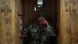 An M23 rebel sitting in a church confessional in eastern DR Congo - Saturday 20 July 2013