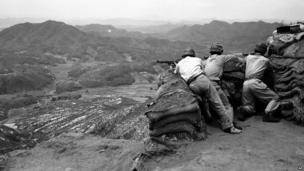 Three South Korean riflemen man a position in the hills as they watch movement of Communist troops in the area beneath them.