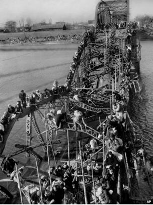Residents from Pyongyang, North Korea, and refugees from other areas crawl over girders of the city's bridge as they flee south to escape the advance of Chinese soldiers