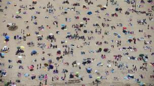 An aerial view shows sunbathers crowding on the beach in Scheveningen during a warm summer day in the Netherlands