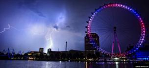 lightning is seen behind The London Eye in central London which is lighted up in the national colors of red, white and blue to mark the birth of the Duke and Duchess of Cambridge's first child.
